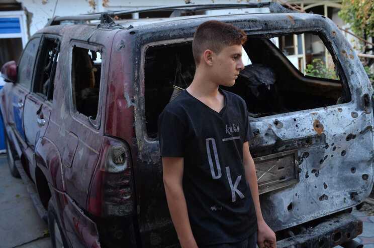 Familiar de Ezmarai Ahmadi junto ao veículo destruído pelos EUA