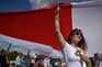 Apoiantes da oposição com a antiga bandeira vermelha e branca da Bielorrússia. Milhares de pessoas juntam-se
