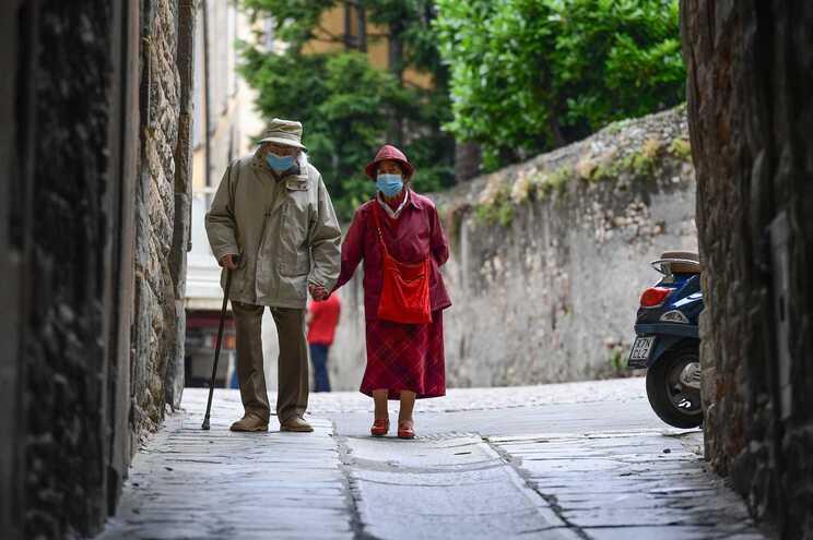 Casal de idosos usa máscara em rua de Bergamo, em Itália