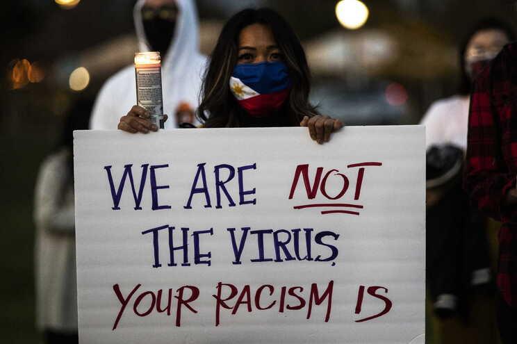 """""""Nós não somos o vírus. O vosso racismo é que é"""", lê-se num cartaz durante uma vigília em Alhambra, na"""