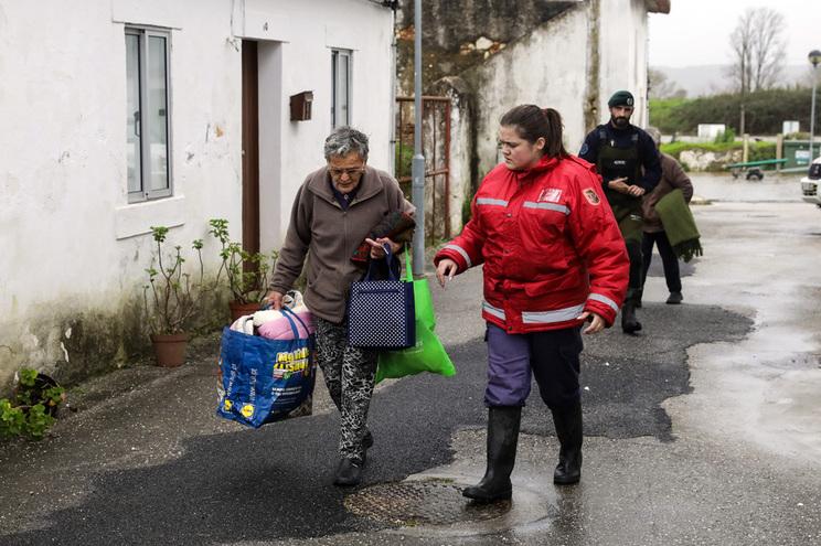 Elementos da proteção civil e da GNR ajudam populares a sair das casas inundadas devido à subida da água