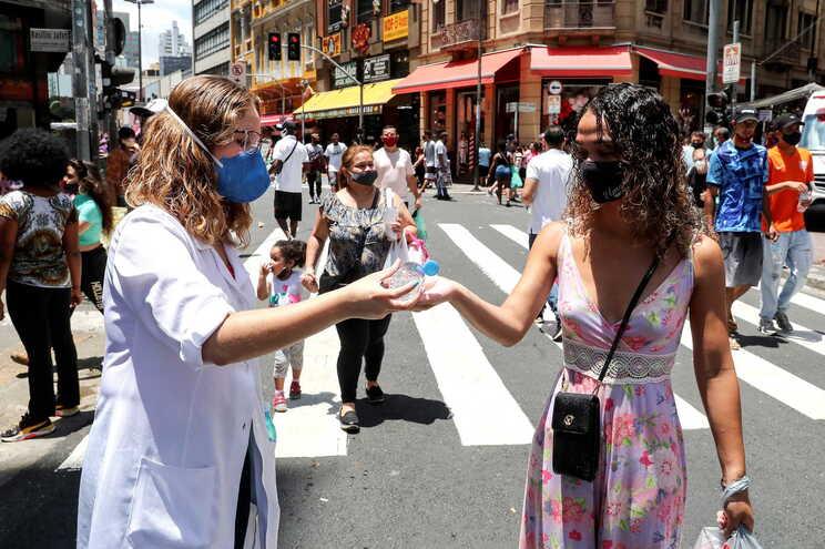 Uma profissional de saúde desinfeta as mãos de pessoas que passam numa movimentada rua comercial de São