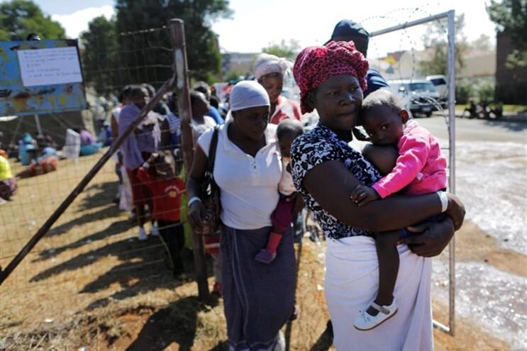 Mulheres e crianças recem ajuda num campo da Cruz Vermelha em Joanesburgo
