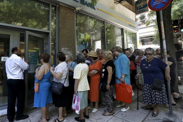Pensionistas esperam junto a uma agência do Banco Nacional para receber parte das suas pensões