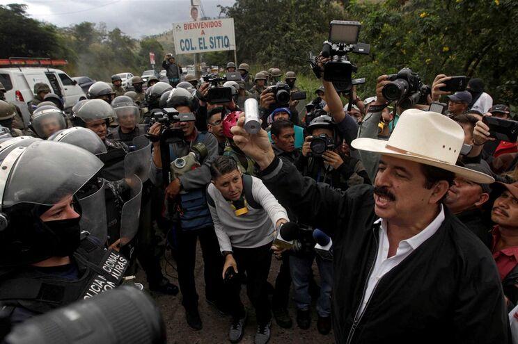 O ex-presidente das Honduras, Manuel Zelaya, mostra uma lata de gás lacrimogéneo para a polícia durante