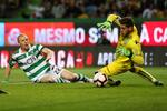 Sporting player Jeremy Mathieu in action against Tondela goalkeeper Claudio Ramos (R) during their Portuguese