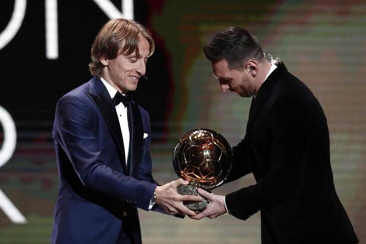Modric, vencedor da edição de 2018 da Bola de Ouro, entrega o troféu a Messi