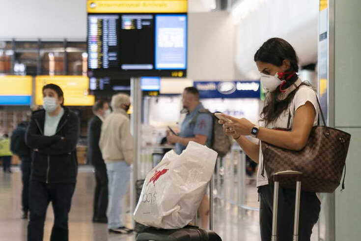epa08472568 A passenger in a protective mask uses her mobile phone at Heathrow Airport, London Britain