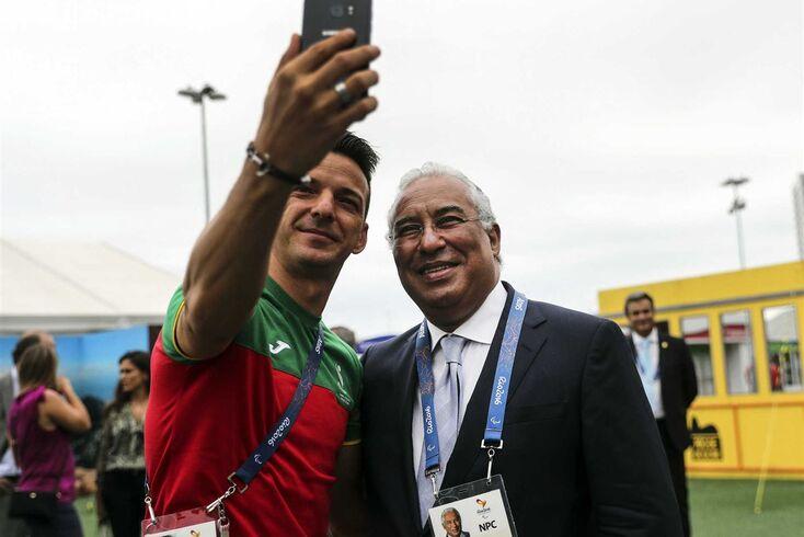 O primeiro-ministro, António Costa,  tira uma foto com o atleta Lenine Cunha durante uma visita à delegação