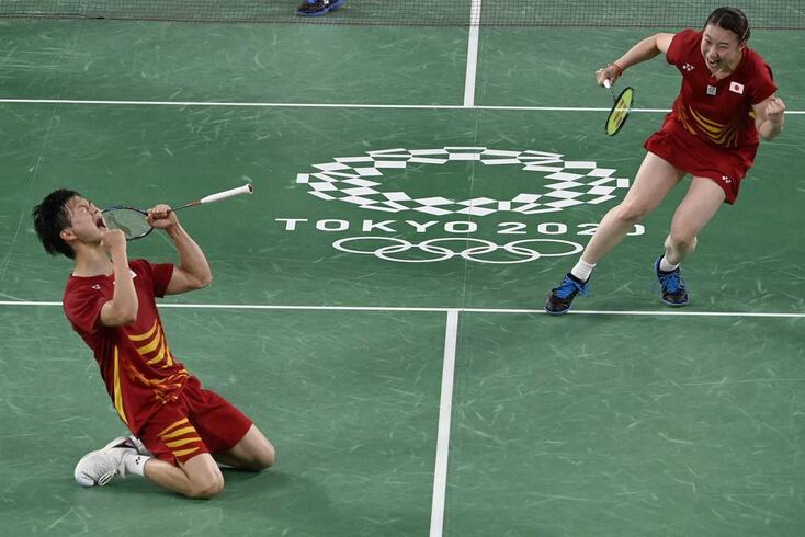Japan's Arisa Higashino and Japan's Yuta Watanabe (L) celebrate after winning their mixed doubles badminton