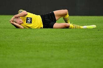 Dortmund's Norwegian forward Erling Braut Haaland lies on the pitch during the German first division