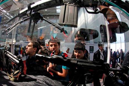 Visitantes olham para uma metralhadora durante a Feira Internacional de Defesa e Segurança do Mar Negro, em Bucareste.