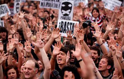 Milhares de pessoas permanecem na praça Puerta del Sol, desafiando a chuva e a proibição ao protesto por parte das autoridades