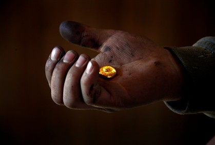 Foto de arquivo da agência Reuters mostra a mão de um homem que segura um pedaço de ouro que foi fundido