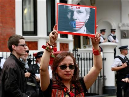 Mulher protesta contra as autoridades britânicas com imagem de Assange em frente à embaixada do Equador em Londres