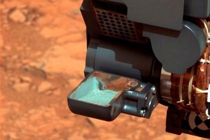 Curiosity recolhendo as primeiras amostras cinzentas do subsolo marciano
