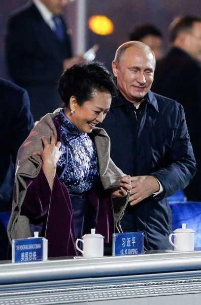 Presidente russo, Vladimir Putin, cobre as costas da primeira dama chinesa Peng Liyuan numa noite fria
