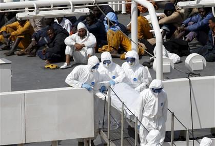Os corpos de 24 vítimas do naufrágio de domingo ao largo da Líbia são retirados do barco da Guarda Costeira, sob o olhar de 28 sobreviventes. A bordo da embarcação naufragada podiam ir 900 pessoas